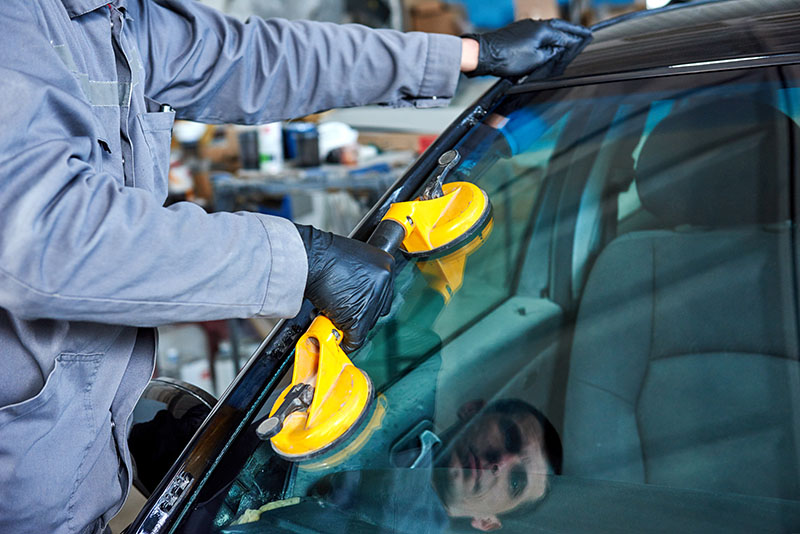 mobile windshield repair. Man replacing windshield pictured