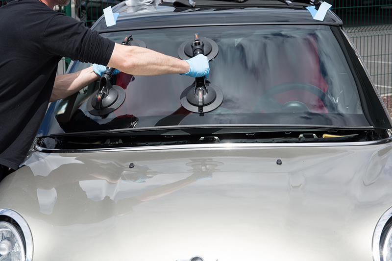 mobile windshield replacement. technician placing windshield