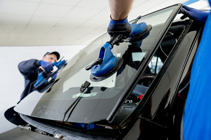 mobile windshield replacement. Technicians replacing a windshield